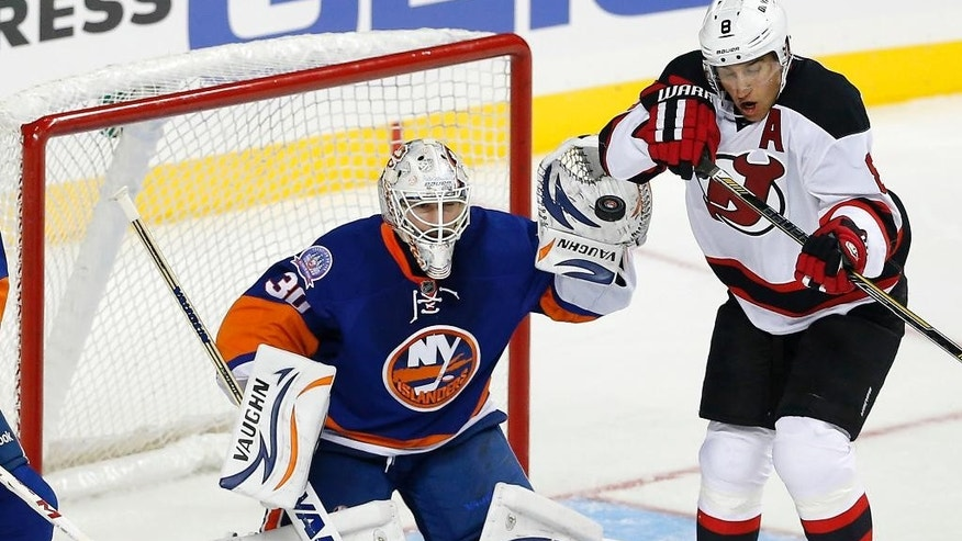 New York Islanders goalie Chad Johnson (30) stops a shot in front of New Jersey Devils right wing Dainius Zubrus (8) in the first period of a preseason NHL hockey game Friday, Sept. 26, 2014, in New York. (AP Photo/Paul Bereswill)