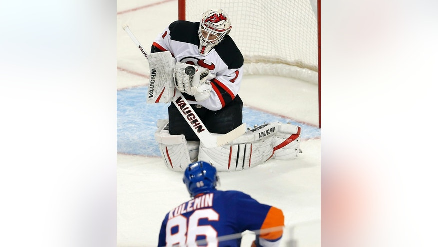 New Jersey Devils goalie Keith Kinkaid (1) makes a save on a shot by New York Islanders left wing Nikolay Kulemin (86) in the first period of a preseason NHL hockey game Friday, Sept. 26, 2014, in New York. (AP Photo/Paul Bereswill)