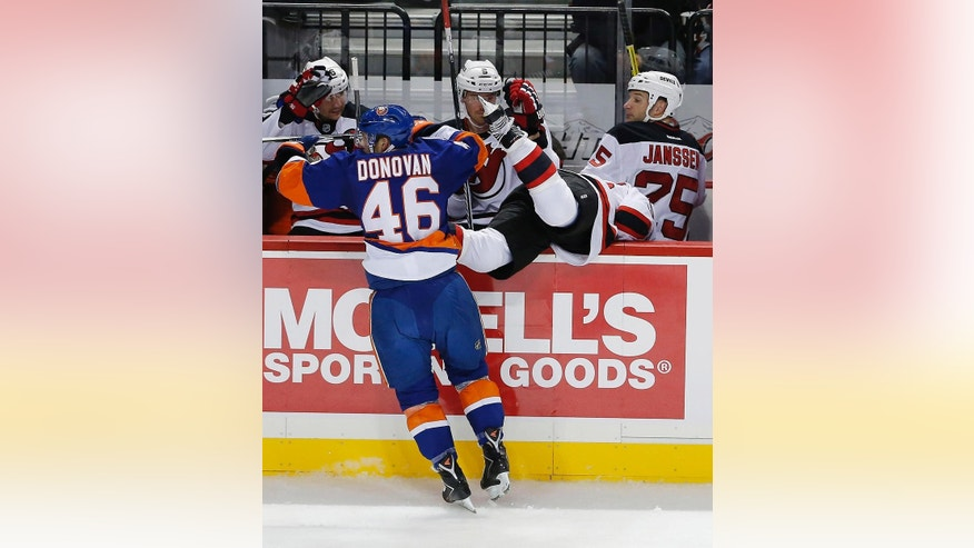 New York Islanders defenseman Matt Donovan (46) sends New Jersey Devils defenseman Peter Harrold flying into the Devils' bench in the first period of a preseason NHL hockey game Friday, Sept. 26, 2014, in New York. (AP Photo/Paul Bereswill)