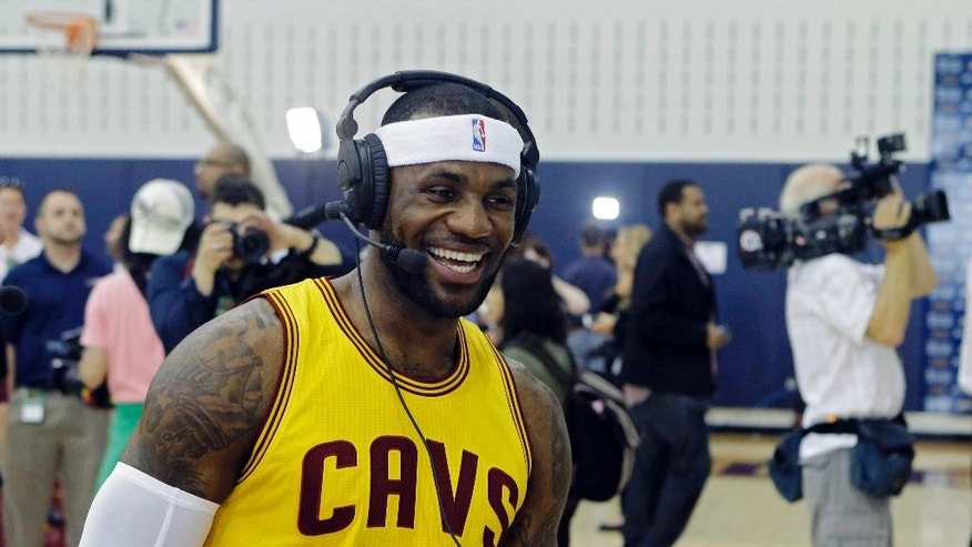 Cleveland Cavaliers' LeBron James laugh during a radio interview during NBA basketball media day in Independence, Ohio  Friday, Sept. 26, 2014. (AP Photo/Mark Duncan)