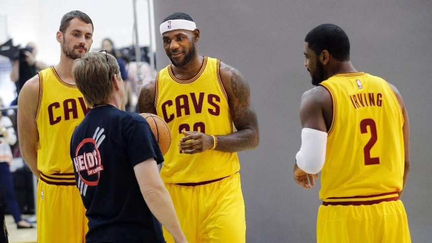 Clevleand Cavaliers' Kevin Love, left, LeBron James and Kyrie Irving (2) get ready for a photo shoot with Sports Illustrated during the NBA basketball team's media day Friday, Sept. 26, 2014, in Independence, Ohio. (AP Photo/Mark Duncan)