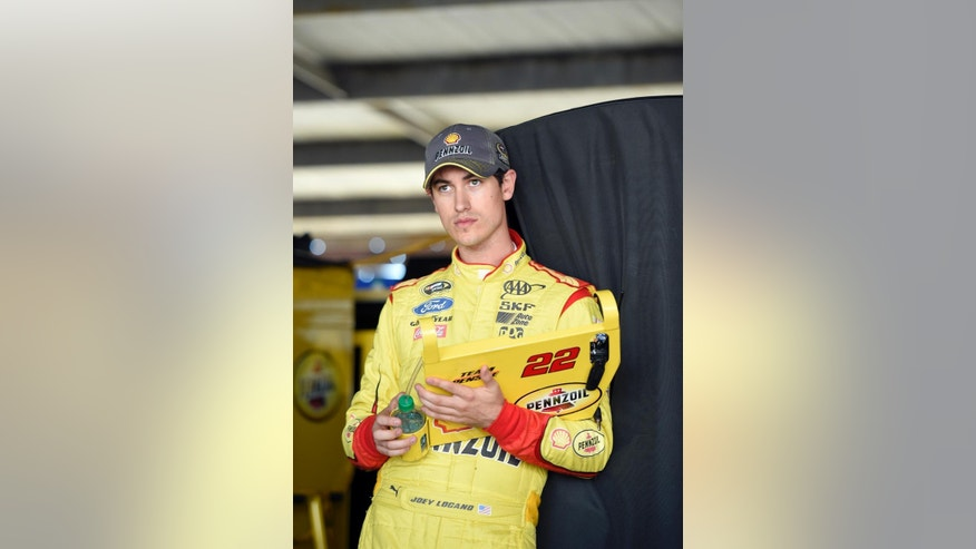 Driver Joey Logano looks on from the garage during practice for the NASCAR Sprint Cup series auto race, Friday, Sept. 26, 2014, at Dover International Speedway in Dover, Del. (AP Photo/Nick Wass)