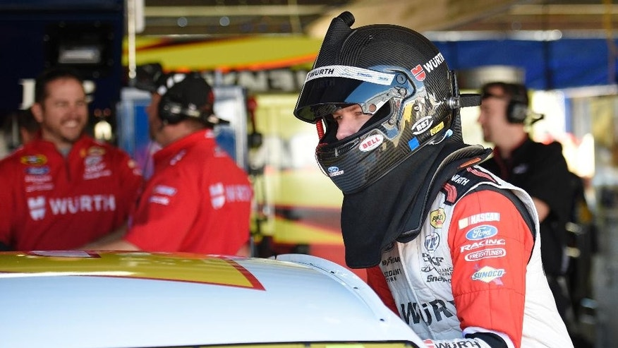 Brad Keselowski climbs into his car before practice for the NASCAR Sprint Cup series auto race, Friday, Sept. 26, 2014, at Dover International Speedway in Dover, Del. (AP Photo/Nick Wass)