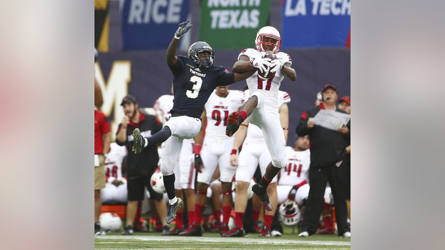 Louisville's James Quick (17) out jumps Florida Internationals Richard Leonard (3) to catch a touch down pass during the first half of an NCAA college football game in Miami, Fla., Saturday, Sept. 20, 2014. (AP Photo/J Pat Carter)