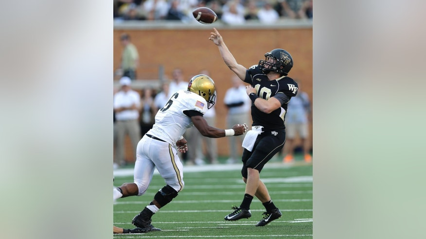 Wake Forest quarterback John Wolford (10) throws a pass over Army defensive back Geoffery Bacon (6) during the second half of an NCAA college football game in Winston-Salem, N.C., Saturday, Sept. 20, 2014. Wake Forest won 24-21. (AP Photo/Chuck Burton)