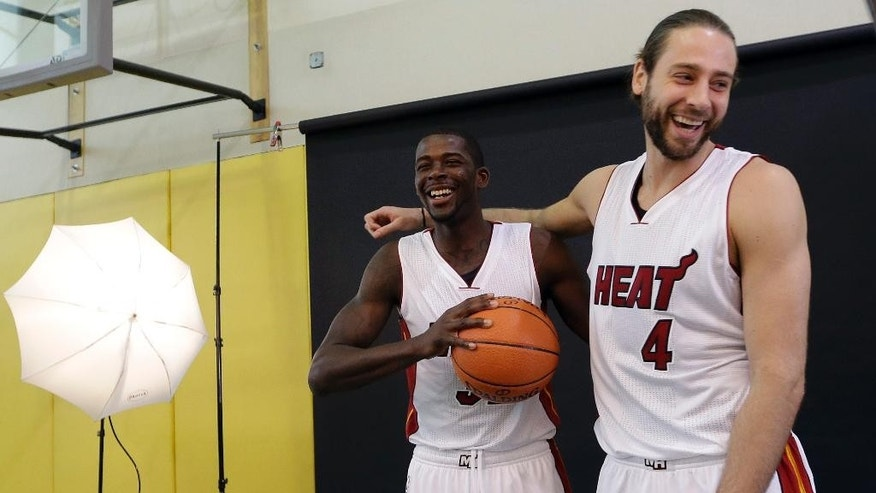 """Miami Heat forward James Ennis, left, is photo """"bombed"""" by forward Josh McRoberts, right, while posing for a photo during NBA basketball media day, Friday, Sept. 26, 2014, in Miami. (AP Photo/Lynne Sladky)"""