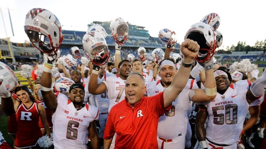Rutgers head coach Kyle Flood, center, celebrates with his team after an NCAA college football game against Navy in Annapolis, Md., Saturday, Sept. 20, 2014. Rutgers won 31-24. (AP Photo/Patrick Semansky)