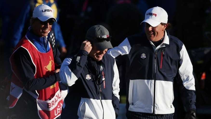 US team captain Tom Watson, center, and Phil Mickelson, right, walk along the fairway from the 1st tee box during the fourball match on the first day of the Ryder Cup golf tournament, at Gleneagles, Scotland, Friday, Sept. 26, 2014. (AP Photo/Scott Heppell)