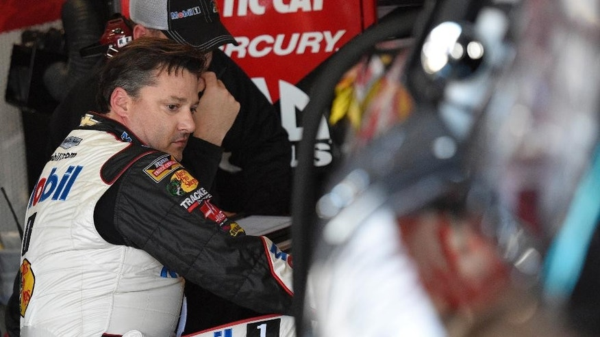 Driver Tony Stewart looks on from the garage area during practice for the NASCAR Sprint Cup series auto race, Friday, Sept. 26, 2014, at Dover International Speedway in Dover, Del. (AP Photo/Nick Wass)