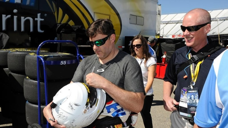 Driver Tony Stewart, left, signs a helmet for fan after practice for the NASCAR Sprint Cup series auto race, Friday, Sept. 26, 2014, at Dover International Speedway in Dover, Del. (AP Photo/Nick Wass)