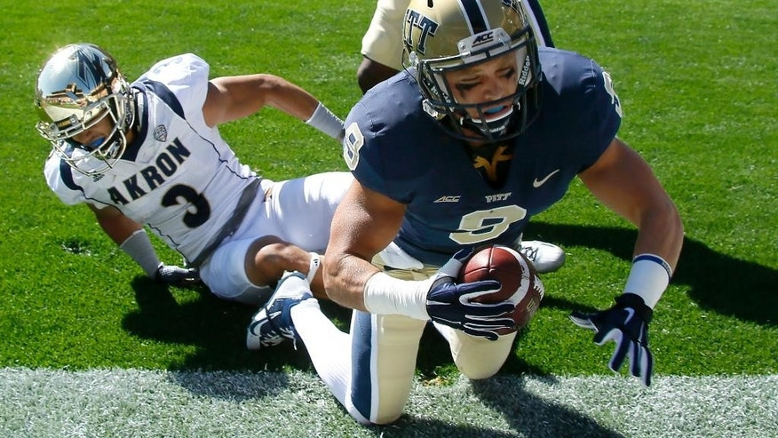 Pittsburgh defensive back Ray Vinopal (9) falls out of the end zone after intercepting a pass intended for Akron wide receiver L.T. Smith (3) in the first quarter of the NCAA college football game on Saturday, Sept. 27, 2014 in Pittsburgh. (AP Photo/Keith Srakocic)