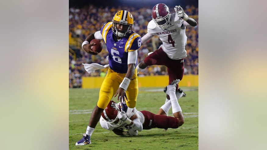LSU quarterback Brandon Harris (6) carries on a keeper near the goal line as New Mexico State defensive back Adaryan Jones (19) and defensive back Winston Rose (4) pursue in the first half of an NCAA college football game in Baton Rouge, La., Saturday, Sept. 27, 2014. (AP Photo/Gerald Herbert)