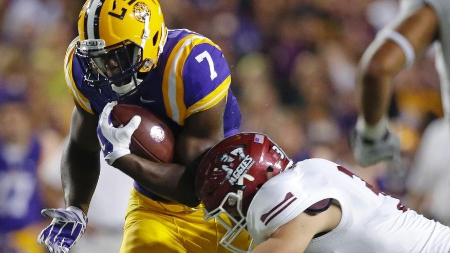LSU running back Leonard Fournette (7) carries against New Mexico State defensive back Dalton Herrington (31) in the first half of an NCAA college football game in Baton Rouge, La., Saturday, Sept. 27, 2014. (AP Photo/Gerald Herbert)