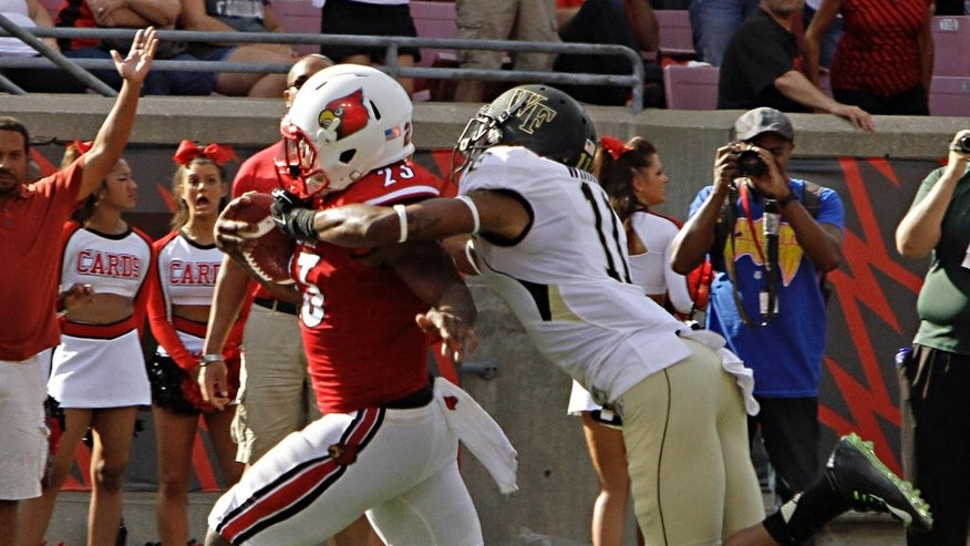 Louisville running back Brandon Radcliff (23) attempts to break a tackle by Wake Forest safety Anthony Wooding, Jr. (11) but continues to complete a 29-yard scoring play in the first half of their NCAA college football game in Louisville, Ky., Saturday, Sept. 27, 2014. (AP Photo/Garry Jones)