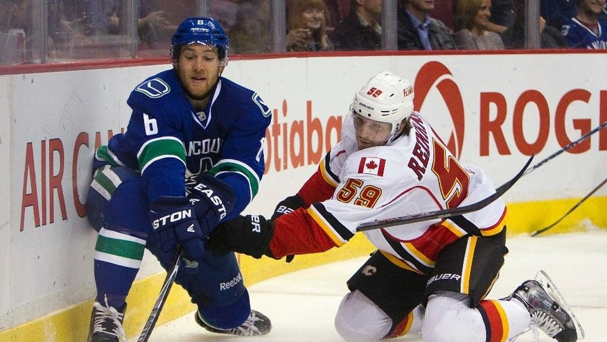 Vancouver Canucks' Yannick Weber (6) fights for the puck against Calgary Flames' Max Reinhart (59) during first-period NHL hockey game action in Vancouver, British Columbia, Friday, Sept. 26, 2014. (AP Photo/The Canadian Press, Ben Nelms)
