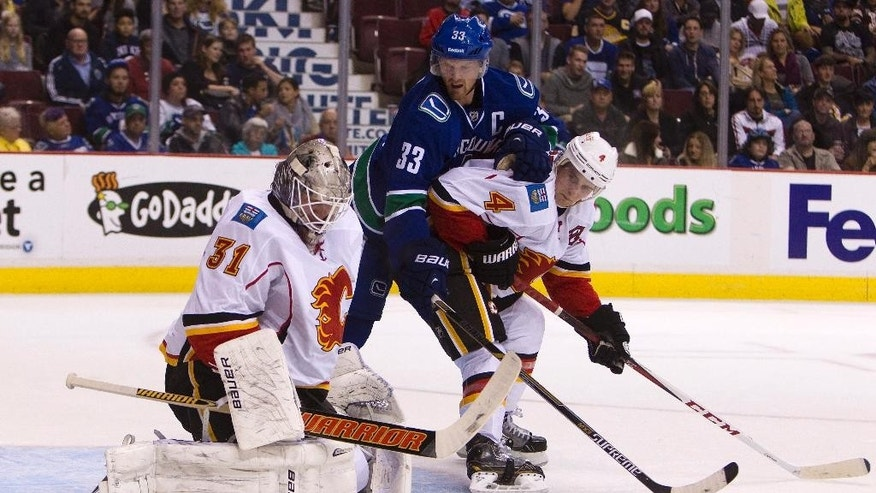 Calgary Flames goaltender Karri Ramo (31) makes a save near teammate Kris Russell (4) and Vancouver Canucks' Henrik Sedin (33) during first-period NHL hockey game action in Vancouver, British Columbia, Friday, Sept. 26, 2014. (AP Photo/The Canadian Press, Ben Nelms)