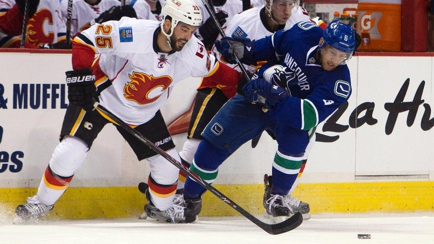 Vancouver Canucks' Yannick Weber (6) fights for the puck against Calgary Flames' Brandon Bollig (25) during first-period NHL hockey game action in Vancouver, British Columbia, Friday, Sept. 26, 2014. (AP Photo/The Canadian Press, Ben Nelms)