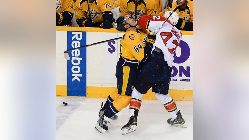 Nashville Predators defenseman Victor Bartley (64) and Florida Panthers center Quinton Howden (42) collide chasing the puck in the first period of a preseason NHL hockey game Saturday, Sept. 27, 2014, in Nashville, Tenn. (AP Photo/Mark Zaleski)