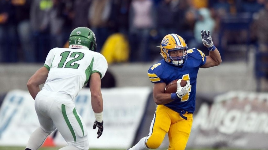 In this photo provided by Montana State University, running back Shawn Johnson (4) navigates North Dakota defenders during the first half of an NCAA football game Saturday, Sept. 27,  2014 in Bozeman, Mont. (AP Photo/Montana State University, Kelly Gorham)