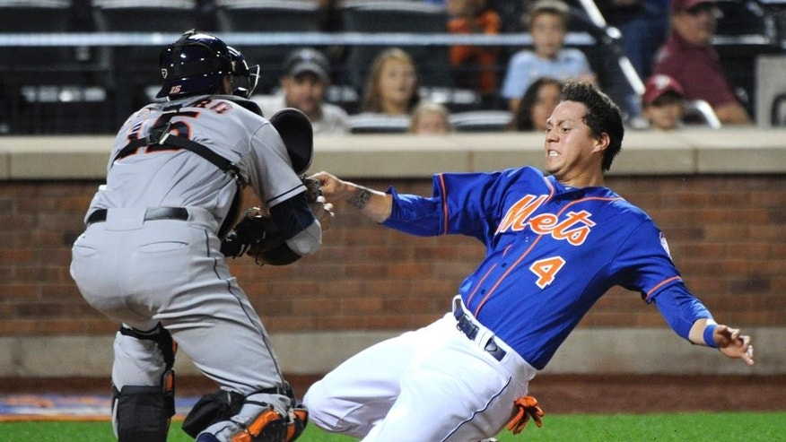 New York Mets' Wilmer Flores (4) is out at home while attempting to score on an infield single by Ruben Tejada as Houston Astros catcher Jason Castro, left, applies the tag during the second inning of an interleague baseball game Saturday, Sept. 27, 2014, at Citi Field in New York. (AP Photo/Bill Kostroun)
