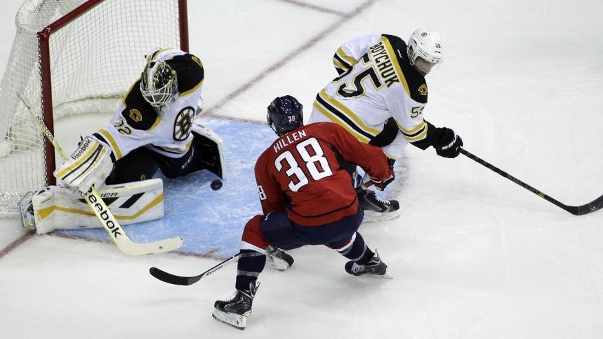 Washington Capitals' Jack Hillen (38) attempts a shot against Boston Bruins goalkeeper Niklas Svedberg, left, of Sweden, as Bruins' Johnny Boychuk (55) defends during the first period of a preseason hockey game, Friday, Sept. 26, 2014, in Washington. The Capitals won 5-4 in overtime. (AP Photo/Luis M. Alvarez)