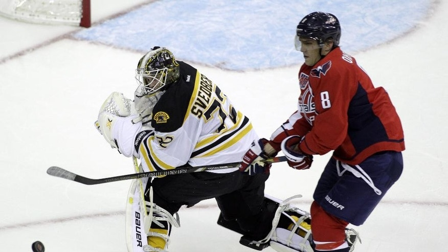 Washington Capitals' Alex Ovechkin (8), of Russia, follows the puck as Boston Bruins goalkeeper Niklas Svedberg, of Sweden, defends during the first period of a preseason hockey game, Friday, Sept. 26, 2014, in Washington. The Capitals won 5-4 in overtime. (AP Photo/Luis M. Alvarez)