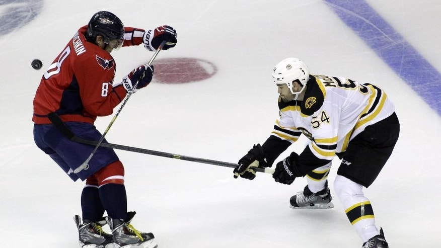 Washington Capitals' Alex Ovechkin (8), of Russia, and Boston Bruins' Adam McQuaid (54) battle for the puck during the second period of a preseason hockey game, Friday, Sept. 26, 2014, in Washington. The Capitals won 5-4. (AP Photo/Luis M. Alvarez)