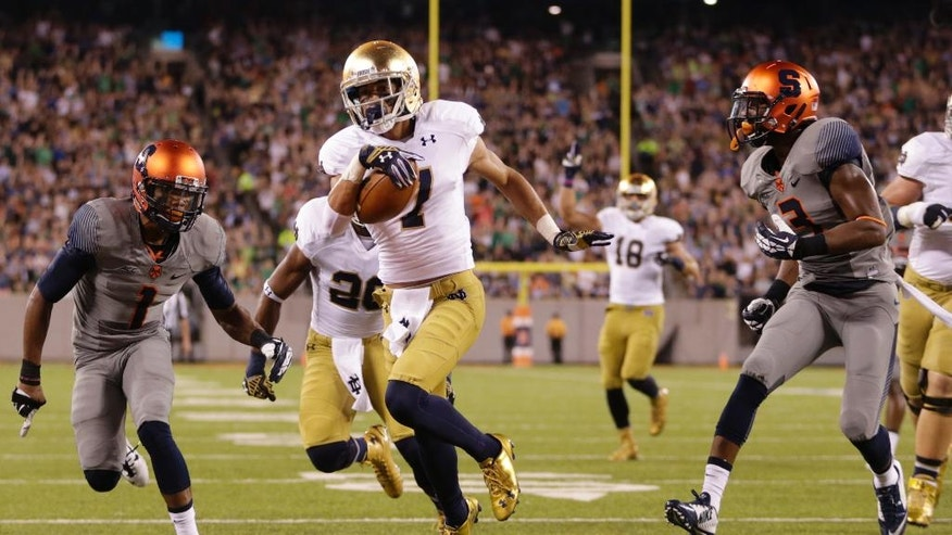 Notre Dame wide receiver William Fuller (7) scores a touchdown as Syracuse cornerback Julian Whigham (1) and safety Durell Eskridge (3) chase him during the first half of an NCAA college football game, Saturday, Sept. 27, 2014, in East Rutherford, N.J. (AP Photo/Julio Cortez)
