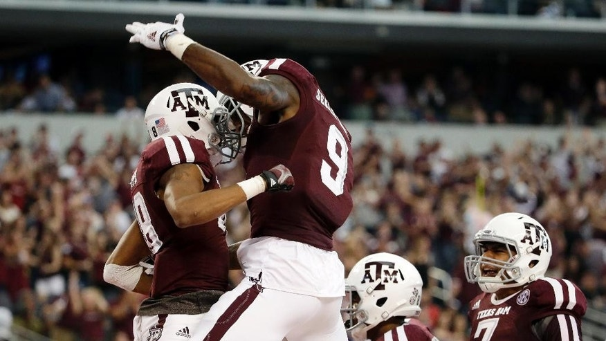 Texas A&M wide receiver Edward Pope, left, celebrates with Ricky Seals-Jones (9) and Kenny Hill (7) after Pope grabbed a pass from Hill for a touchdown against Arkansas in the first half of an NCAA college football game, Saturday, Sept. 27, 2014, in Arlington, Texas. (AP Photo/Tony Gutierrez)