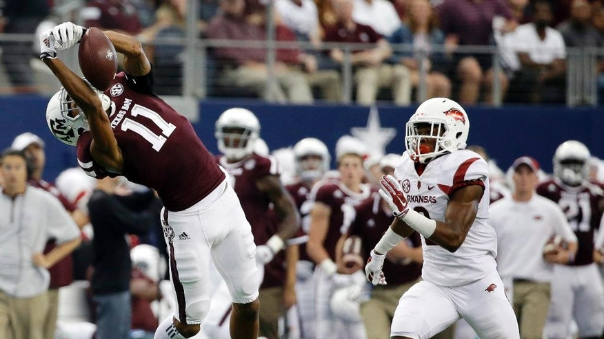 Texas A&M wide receiver Josh Reynolds (11) is unable to come down with a pass from Kenny Hill as Arkansas cornerback D.J. Dean (2) defends in the first half of an NCAA college football game, Saturday, Sept. 27, 2014, in Arlington, Texas. (AP Photo/Tony Gutierrez)