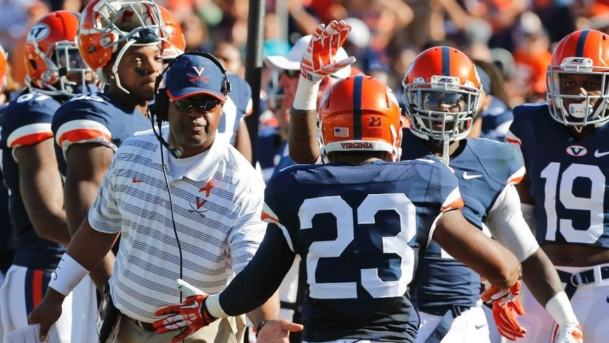 Virginia running back Khalek Shepherd (23) is welcomed back to the bench by head coach Mike London, left, after a score during the first half of an NCAA college football game in Charlottesville, Va., Saturday, Sept. 27, 2014.   (AP Photo/Steve Helber)