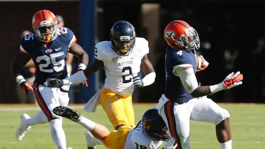 Virginia running back Taquan Mizzell (4) gains yardage as Kent State safety Nate Holley (18) makes the stop during the first half of an NCAA college football game in Charlottesville, Va., Saturday, Sept. 27, 2014.   (AP Photo/Steve Helber)