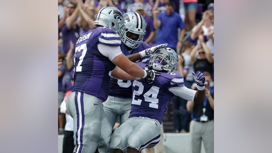 Kansas State running back Charles Jones (24) celebrates with teammates Boston Stiverson, left, and Deante Burton, center, after Jones scored a touchdown during the first half of an NCAA college football game against UTEP Saturday, Sept. 27, 2014, in Manhattan, Kan. (AP Photo/Charlie Riedel)
