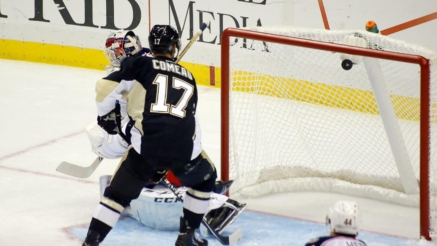 The puck gets past Columbus Blue Jackets goalie Sergei Bobrovsky, left, and Pittsburgh Penguins left wing Blake Comeau on a shot by Penguins' Kasperi Kapanen for a goal in the first period of the NHL pre-season hockey game, Saturday, Sept. 27, 2014 in Pittsburgh. (AP Photo/Keith Srakocic)