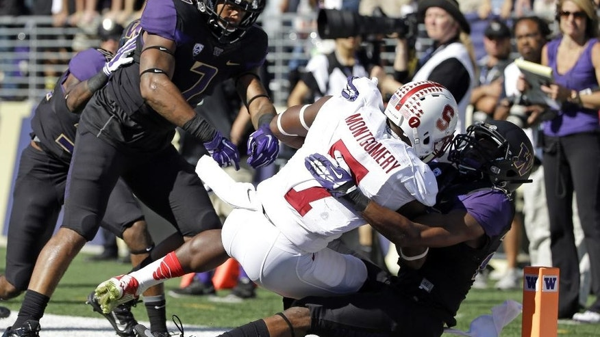 Stanford's Ty Montgomery (7) falls into the end zone for touchdown as Washington's Trevor Walker pulls him down, followed by Shaq Thompson in the first half of an NCAA football game Saturday, Sept. 27, 2014, in Seattle. (AP Photo/Elaine Thompson)