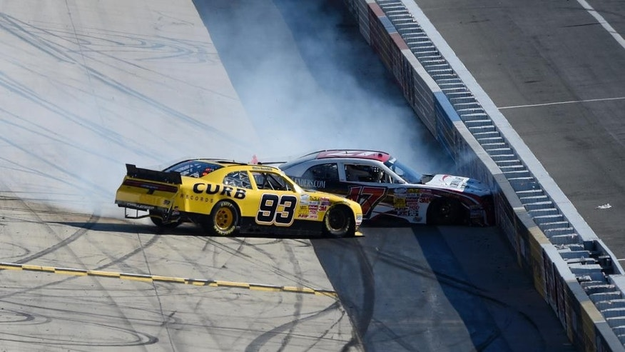 Kevin Swindell (93) wrecks along with Tyler Berryhill (17) during the NASCAR Nationwide series auto race, Saturday, Sept. 27, 2014, at Dover International Speedway in Dover, Del. (AP Photo/Nick Wass)