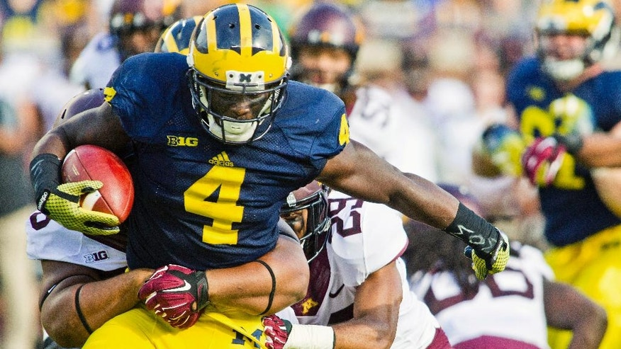 Michigan running back De'Veon Smith (4) tries to break away from Minnesota tackles in the second quarter of an NCAA college football game in Ann Arbor, Mich., Saturday, Sept. 27, 2014. (AP Photo/Tony Ding)