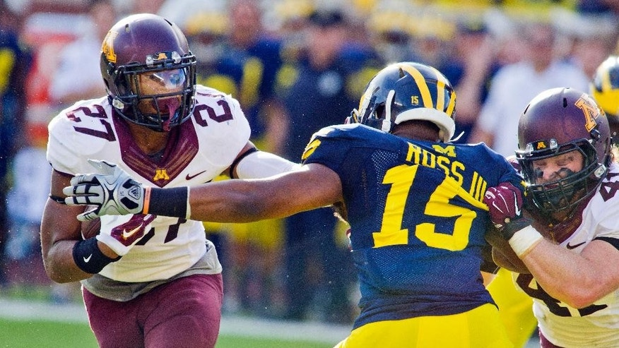 Minnesota running back David Cobb (27) gets an assist to avoid Michigan linebacker James Ross III (15) from teammate Miles Thomas, right, in the second quarter of an NCAA college football game in Ann Arbor, Mich., Saturday, Sept. 27, 2014. (AP Photo/Tony Ding)