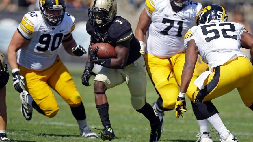 Purdue running back Akeem Hunt (1) cuts through Iowa defenders Louis Trinca-Pasat  (90), Carl Davis (71) and Quinton Alston during the first half of an NCAA college football game in West Lafayette, Ind., Saturday, Sept. 27, 2014. (AP Photo/Michael Conroy)