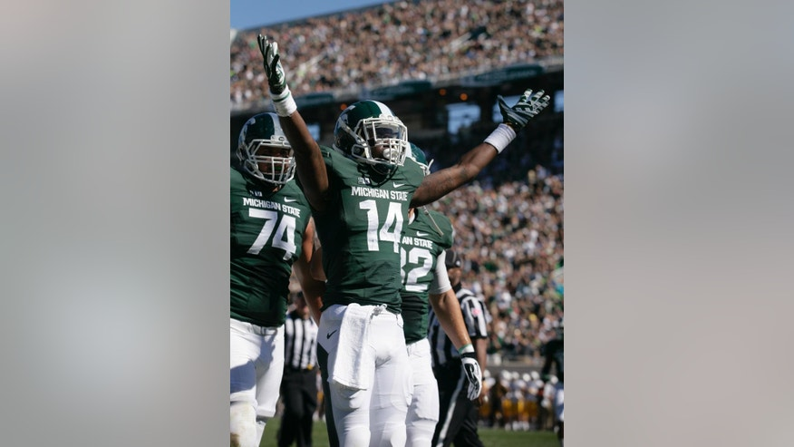 Michigan State's Tony Lippett (14) celebrates his touchdown reception against Wyoming as teammates Jack Conklin (74) and Josiah Price, right, move in to join him during the first quarter of an NCAA college football game, Saturday, Sept. 27, 2014, in East Lansing, Mich. (AP Photo/Al Goldis)