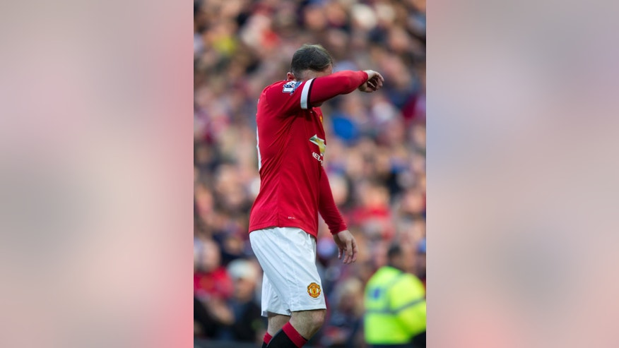 Manchester United's Wayne Rooney walks from the pitch after being shown a red card by referee Lee Mason during his team's English Premier League soccer match against West Ham United at Old Trafford Stadium, Manchester, England, Saturday Sept. 27, 2014. (AP Photo/Jon Super)