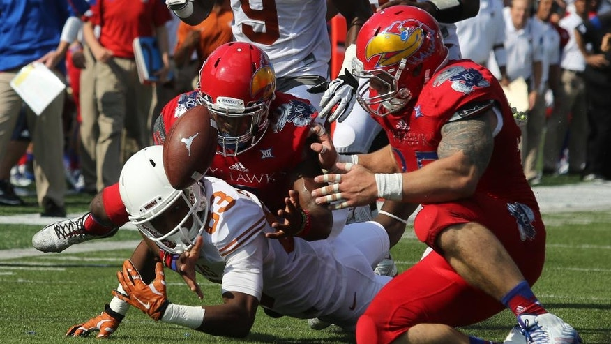Texas' Armanti Foreman (83) fumbles the ball as he is hit by Kansas' Isaiah Johnson, back, and T.J. Semke in the first quarter during an NCAA football game Saturday, Sept. 27, 2014, in Lawrence, Kan. (AP Photo/Ed Zurga)