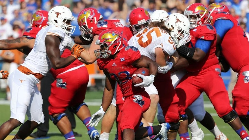 Kansas running back De'Andre Mann finds a hole as he rushes against against Texas in the first quarter during an NCAA football game Saturday, Sept. 27, 2014, in Lawrence, Kan. (AP Photo/Ed Zurga)