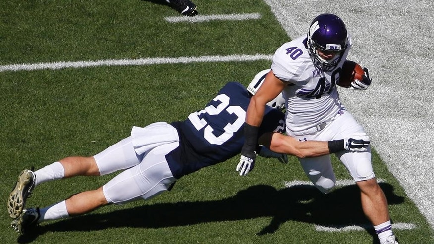 Northwestern's Dan Vitale (40) eludes a tackle by Penn State safety Ryan Keiser (23) after taking a pass from quarterback Trevor Siemian during the first quarter of an NCAA college football game in State College, Pa., Saturday, Sept. 27, 2014. (AP Photo/Gene J. Puskar)