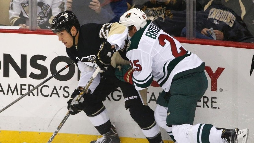 Pittsburgh Penguins' Steve Downie (23) works the puck out around the corner with Minnesota Wild's Jonas Brodin (25) at his back in the first period of an NHL preseason hockey game in Pittsburgh, Thursday, Sept. 25, 2014. (AP Photo/Gene J. Puskar)
