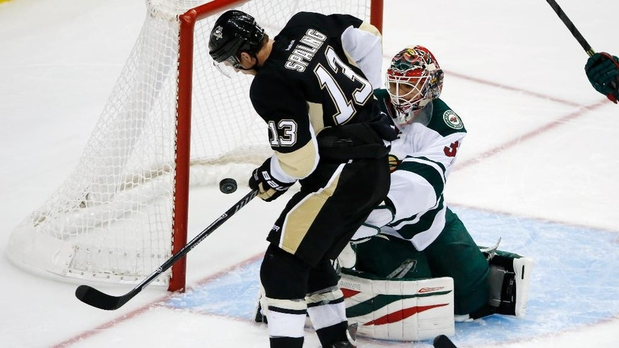 Pittsburgh Penguins' Steve Downie (23) cannot get a rebound past Minnesota Wild goalie Ilya Bryzgalov (30) during the overtime period of an NHL preseason hockey game in Pittsburgh Thursday, Sept. 25, 2014. The Penguins won in overtime 3-2. (AP Photo/Gene J. Puskar)