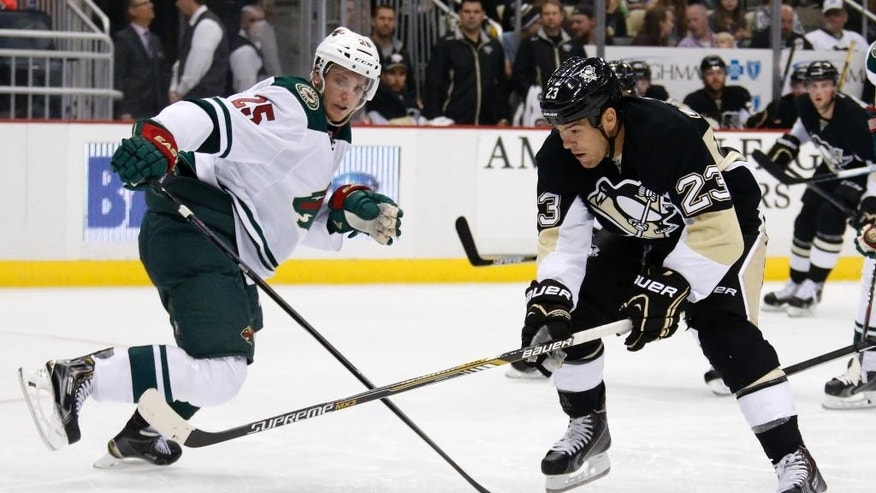 Pittsburgh Penguins' Steve Downie (23) skates past Minnesota Wild's Jonas Brodin (25) but cannot get a shot off in the second period of an NHL preseason hockey game in Pittsburgh, Thursday, Sept. 25, 2014. (AP Photo/Gene J. Puskar)
