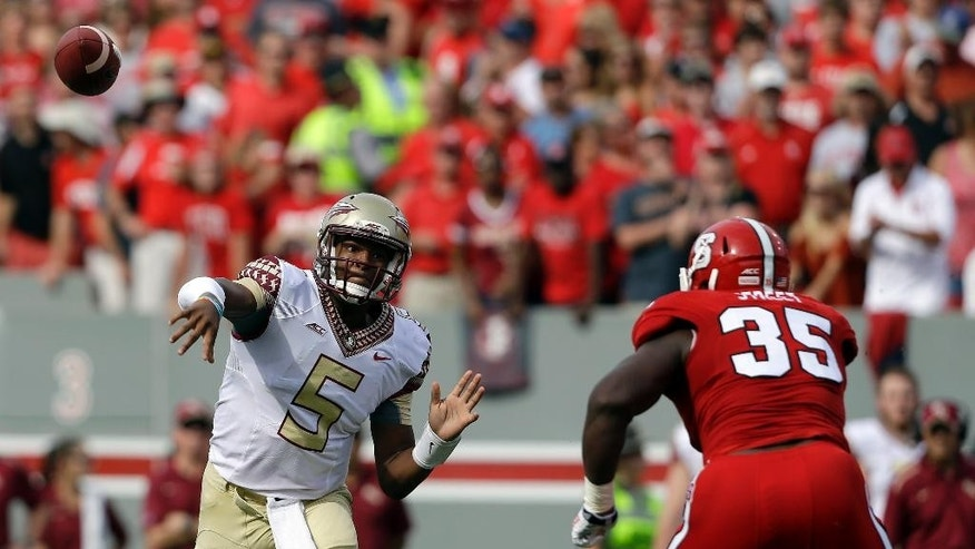 Florida State quarterback Jameis Winston (5) throws a pass as North Carolina State's Kentavius Street (35) rushes during the first half of an NCAA college football game in Raleigh, N.C., Saturday, Sept. 27, 2014. (AP Photo/Gerry Broome)