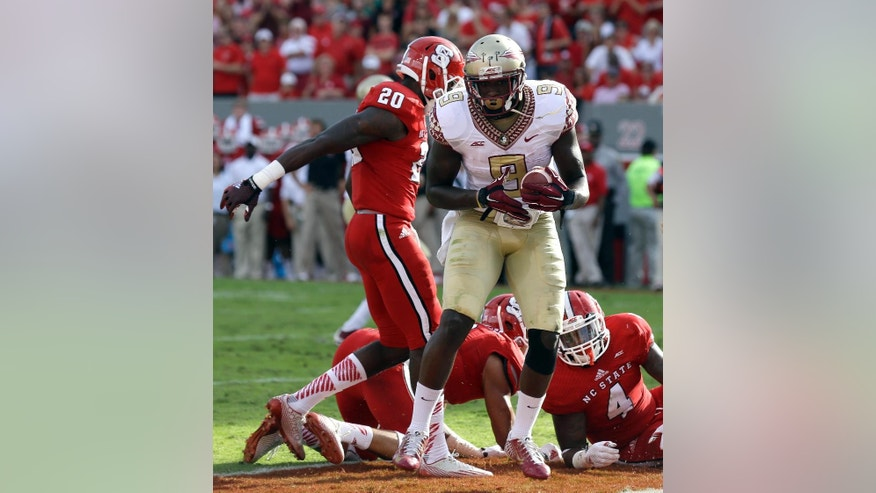 Florida State's Karlos Williams (9) scores against North Carolina State's Hakim Jones (20) and Jerod Fernandez (4) during the first half of an NCAA college football game in Raleigh, N.C., Saturday, Sept. 27, 2014. (AP Photo/Gerry Broome)