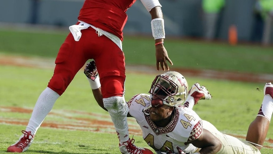 Florida State's DeMarcus Walker (44) loses his helmet chasing North Carolina State quarterback Jacoby Brissett (12) during the first half of an NCAA college football game in Raleigh, N.C., Saturday, Sept. 27, 2014. (AP Photo/Gerry Broome)